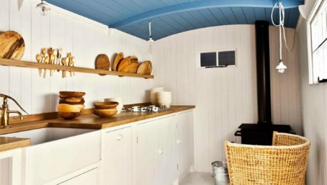 1. Синьо небе. Стилен и свеж интериор за малка и тясна кухня. Оформлечието е предимно в бели тонове, който създават усещане за повече светлина. Забелязва се изобилието от дървени детайли. Синьото небе е акцент и създава динамика. -586_1