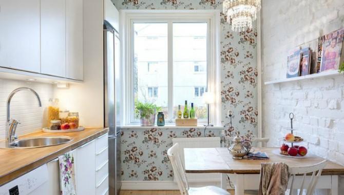 2. Домашен уют. Светла кухня, в чийто интериор се смесват три различни текстури: класическа керамична печка, цветни тапети и каменна зидария. -586_2
